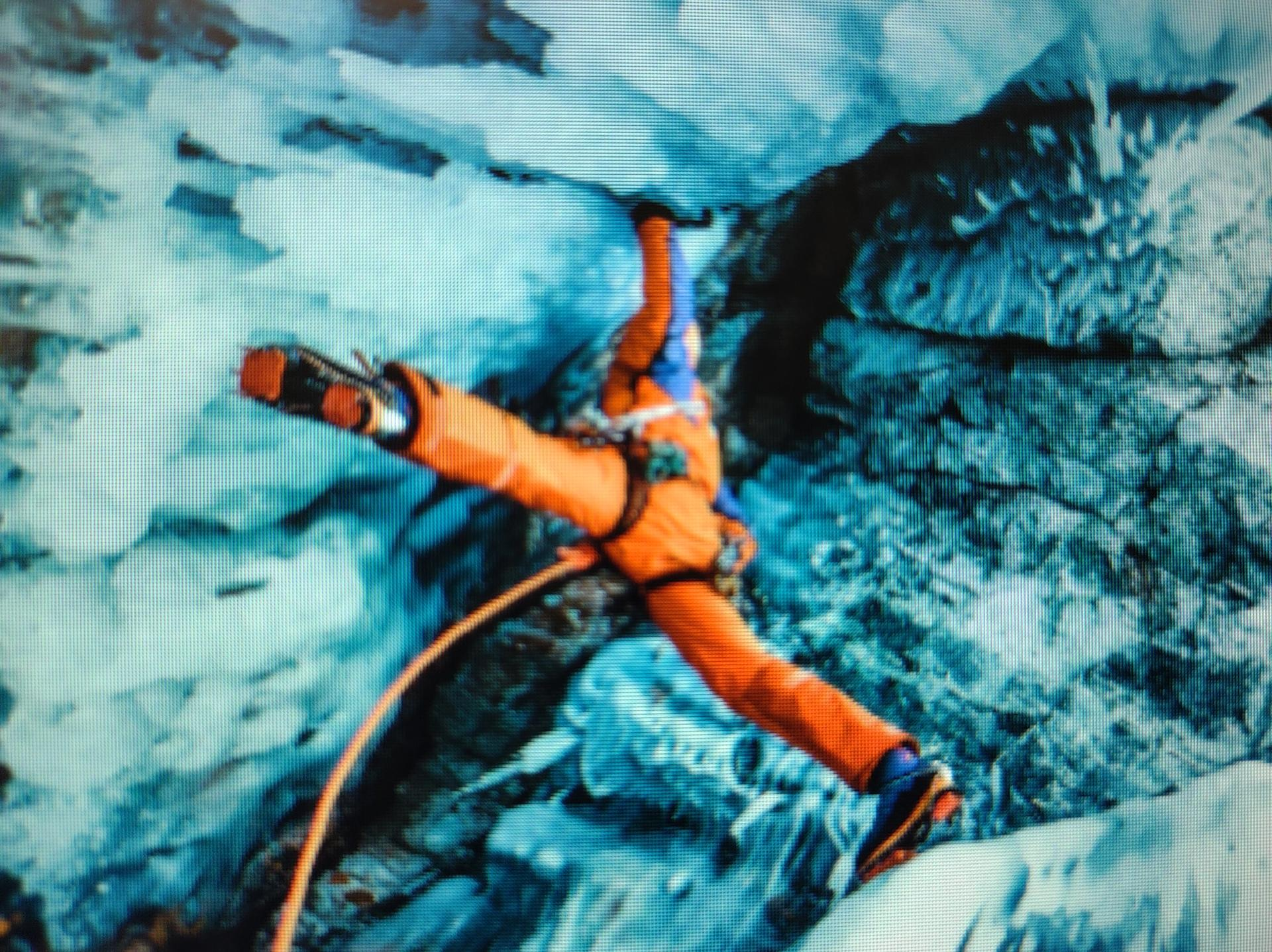 """Mountaineer athlete Dani Arnold explores the deepest lake on earth.  His legs are fully extended in a """"spread eagle"""" position as he makes a perilous climb up a very steep and treacherous ice-covered mountain."""