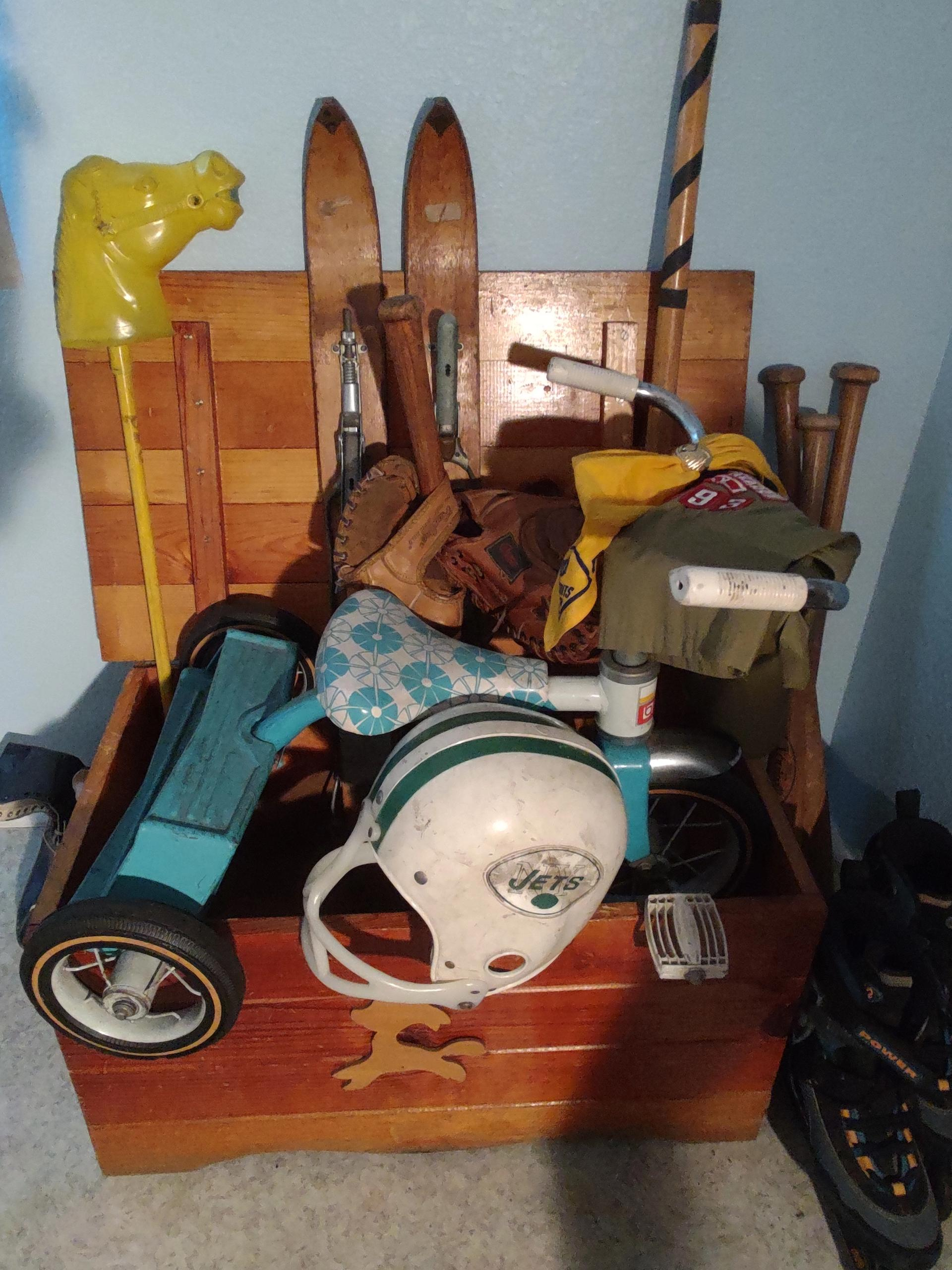 A picture of an old wooden varnished child's crate, containing many childhood sports toys and items, including an old pair of short wooden skis, a stickball bat, four wooden classic baseball bats, a couple of baseball gloves, a NY Jets plastic football helmet, a child's blue and white tricycle, and a pair of in-line skates from yesteryear.