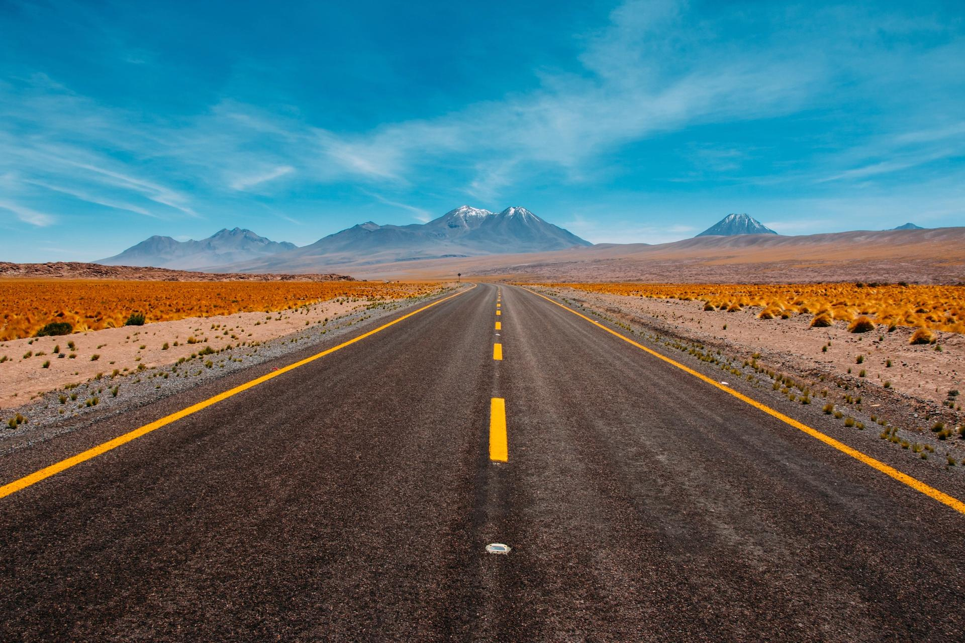 A rural paved one-lane road, with snow-peaked mountains in the far distance.  A glorious blue sky abounds.