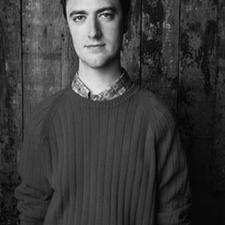 Sean Gunn in a square crop and grey color