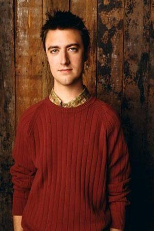 The actor Sean Gunn looking young in a read sweater