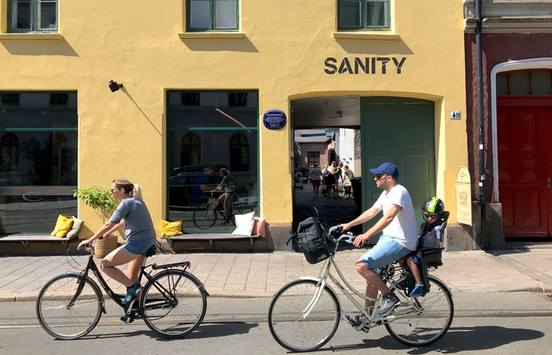 Two cyclists going past the Sanity HQ in Oslo