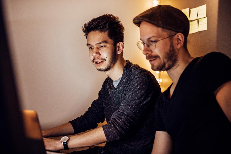 Två utvecklare som samarbetar vid en dator.