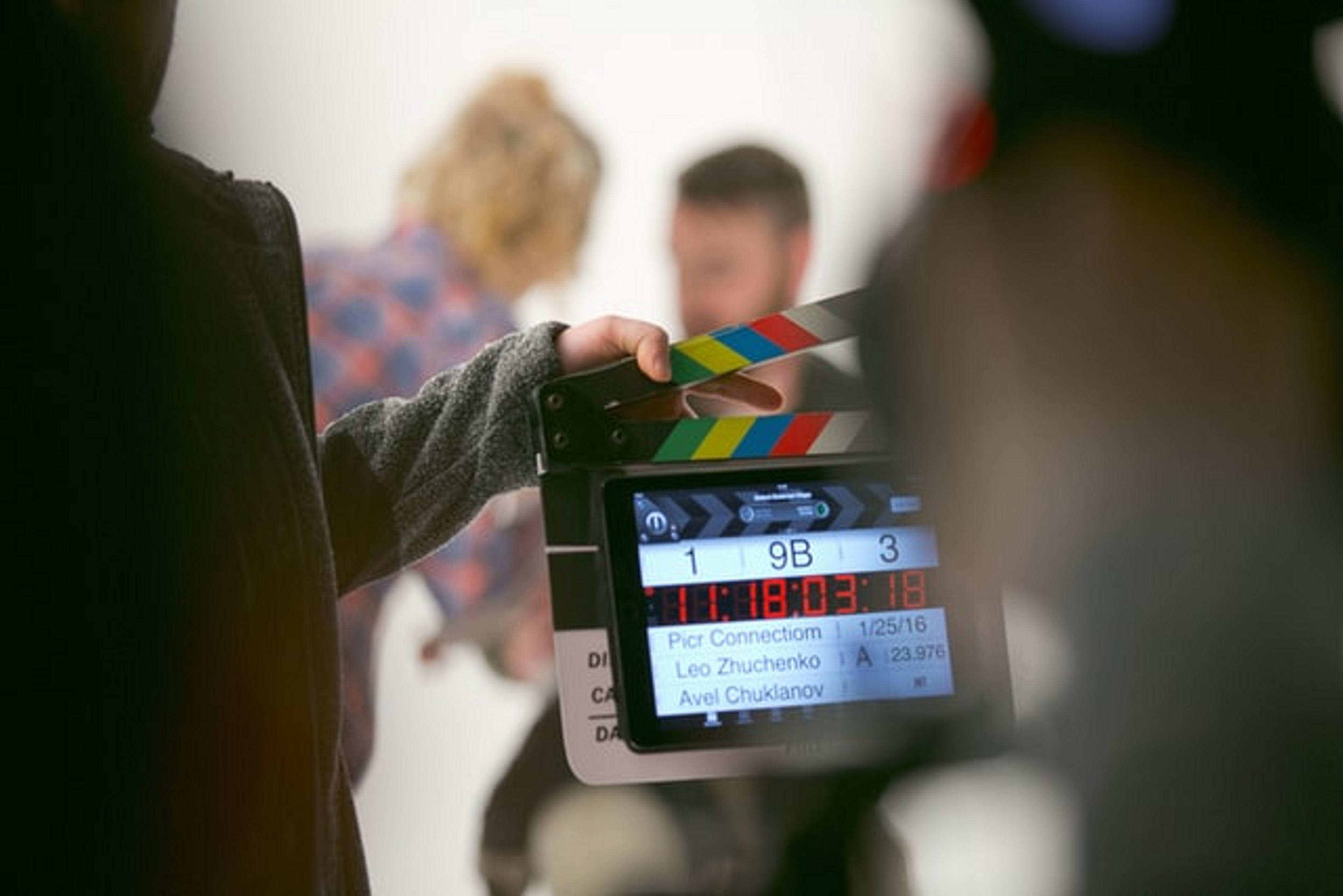 A film slate with actors in the background