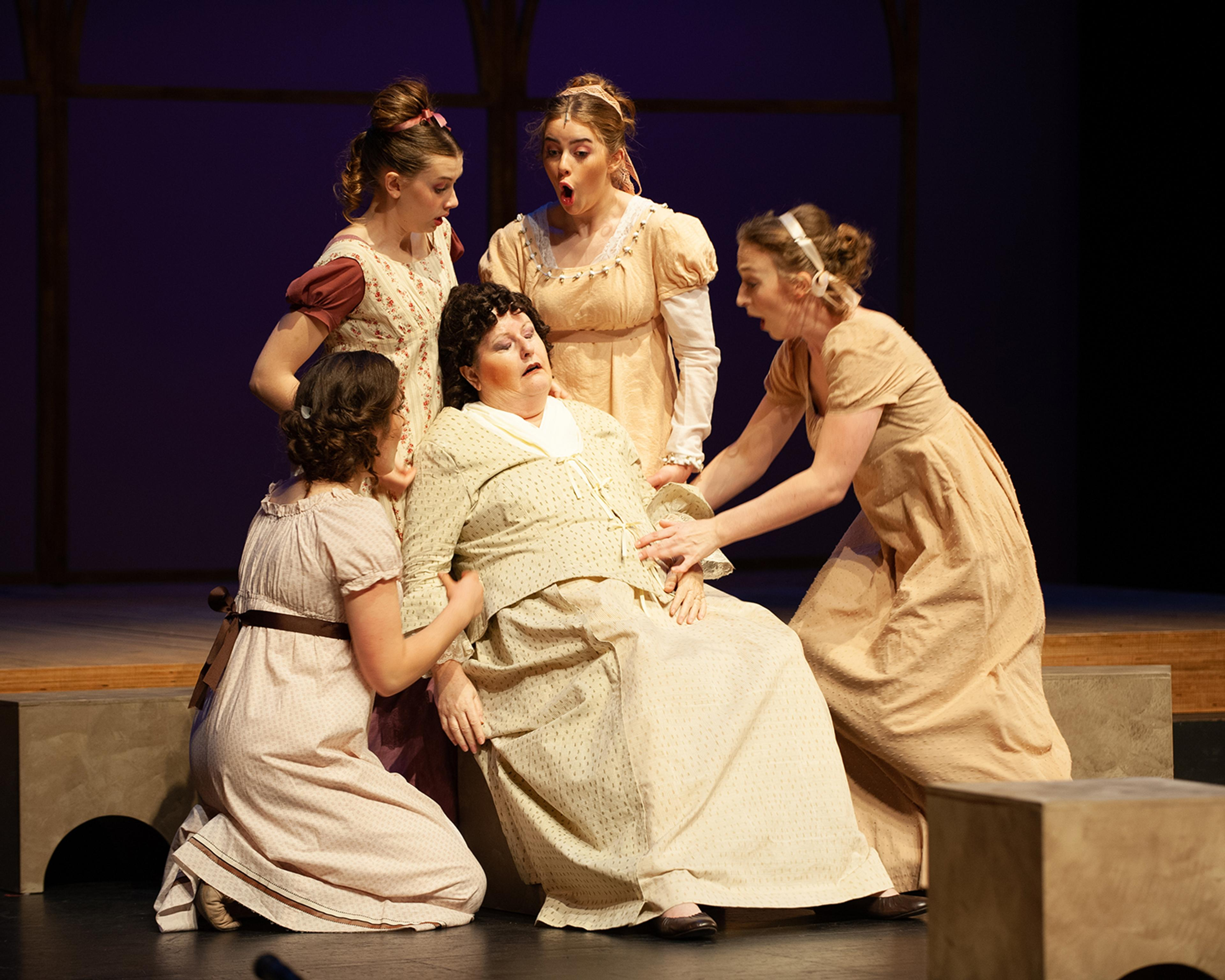 A production photo from Pride and Prejudice with Mrs. Bennet fainting into a chair. Her daughters, who are gathered around her, look shocked.