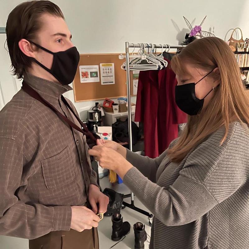 Curtis Maciborski gets his tie tied by costume designer Dani Dejong