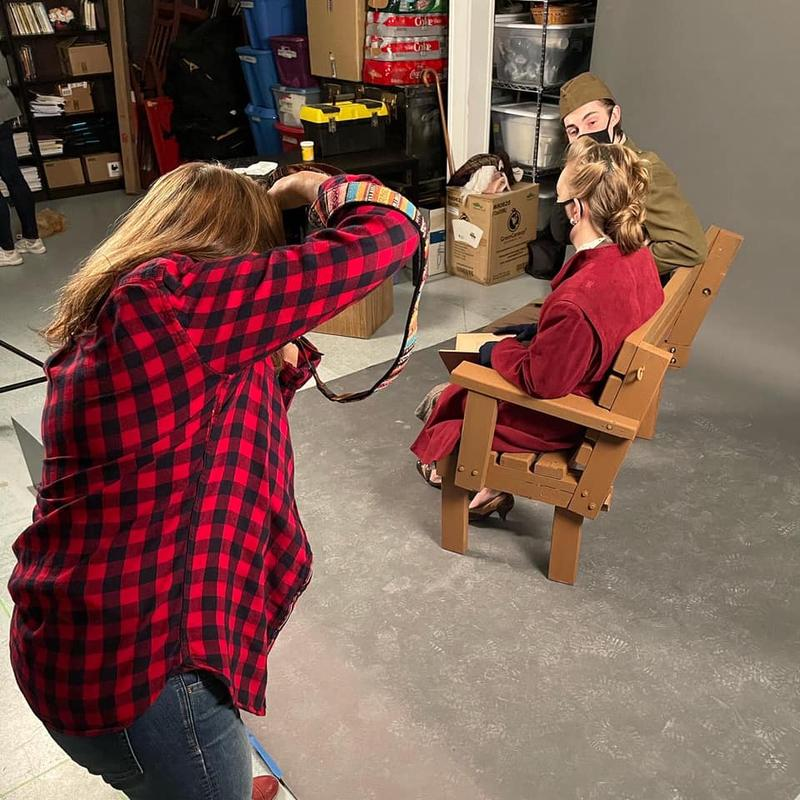 Photographer Dianna Lewis takes a photo of Cassie Unger and Curtis Maciborski, who sit on a bench in 1940s costume.