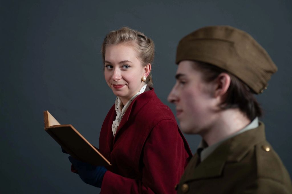 Cassie Unger as May looks at Curtis Maciborski slyly while reading a book.