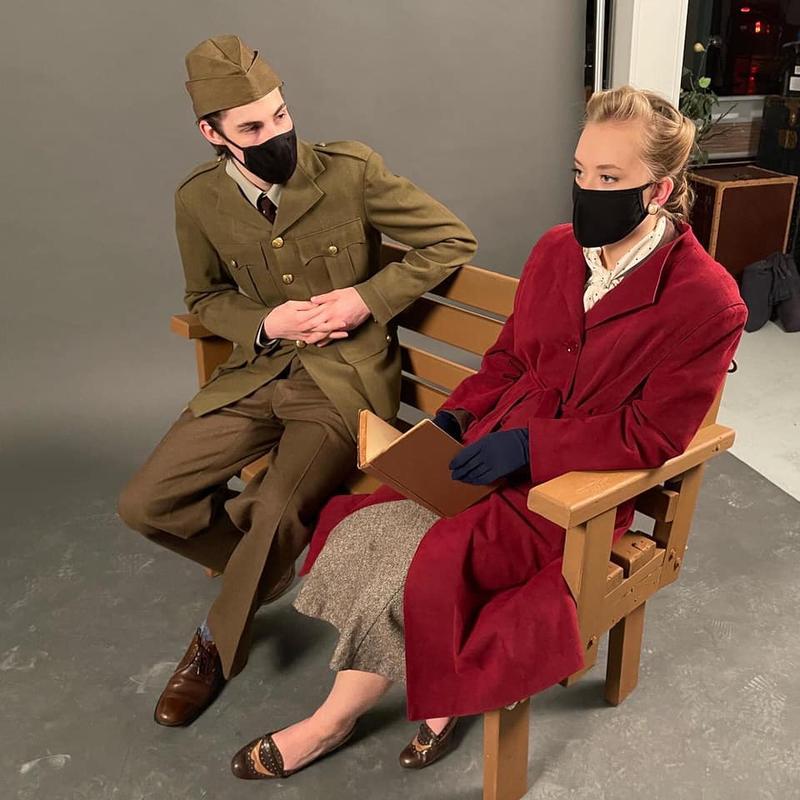 Cassie Under and Curtis Maciborski in 1940s costume sitting on a bench.