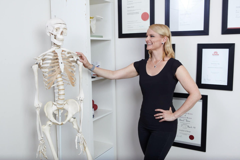 Karen Finnin standing next to a medical model of a human skeleton