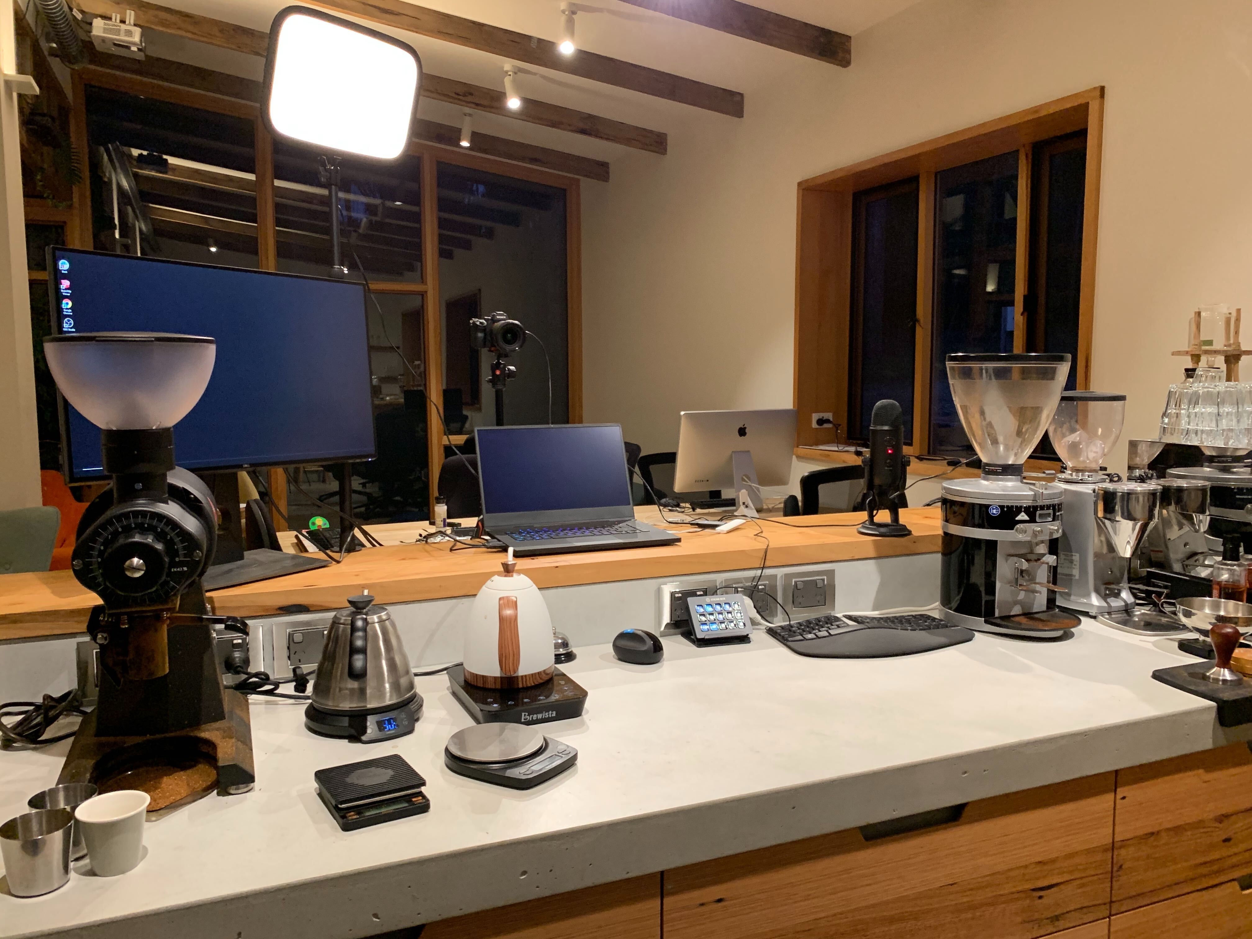 Joel's coffee bar set up at night, featuring all his coffee making tools and broadcast equipment