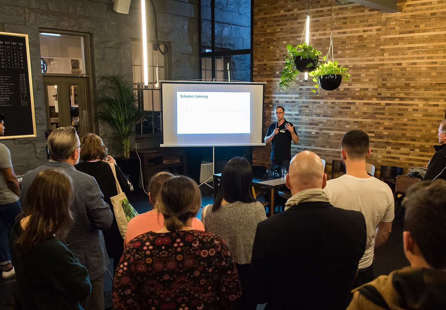 A photo of a person giving a presentation to an audience at the first Cliniko Community meetup in Melbourne.
