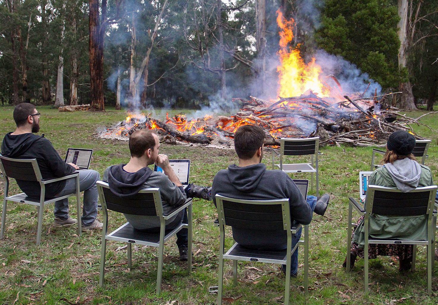 A photo of some members of the Cliniko team stood around a bonfire.