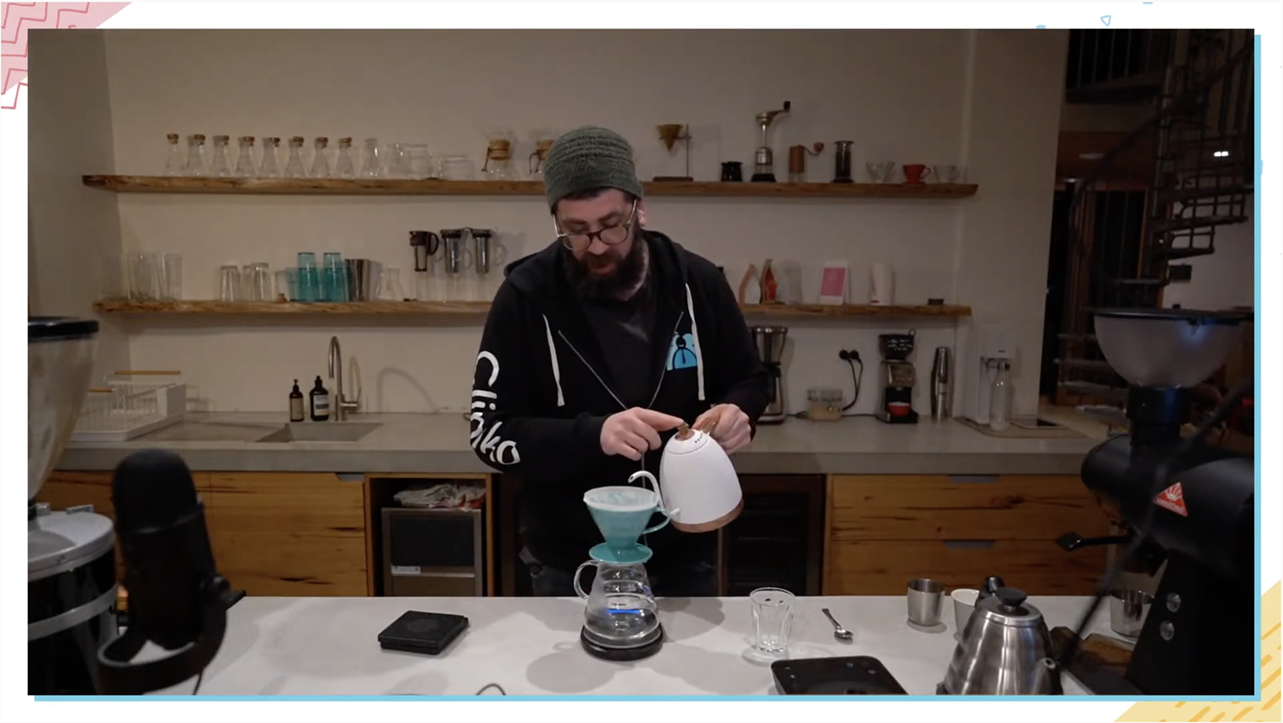 A screenshot of Joel pouring hot water from a kettle into his V60 to brew pour over coffee