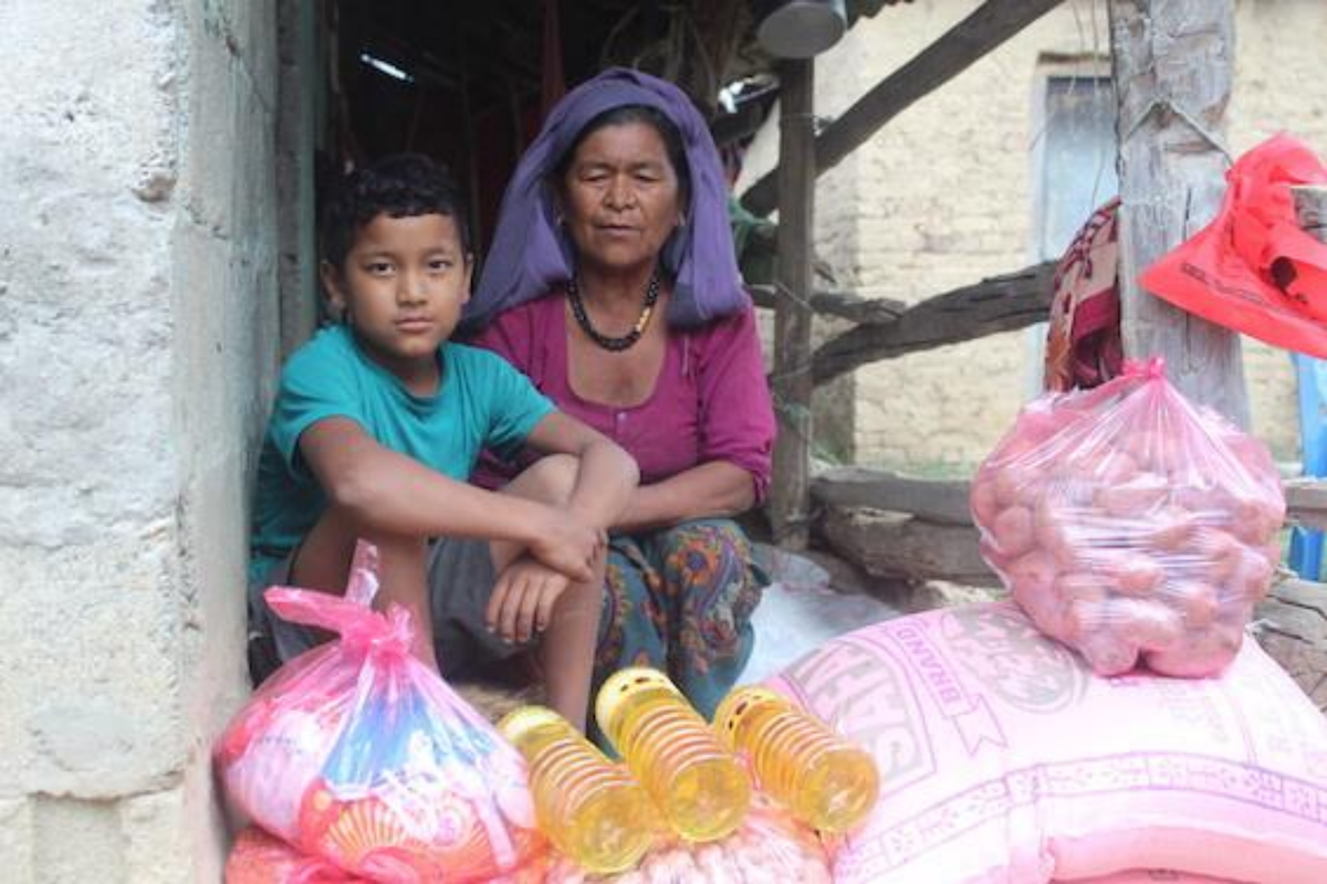 A boy and a woman sitting behind bags of rice, potatoes, and bottles of cooking oil.