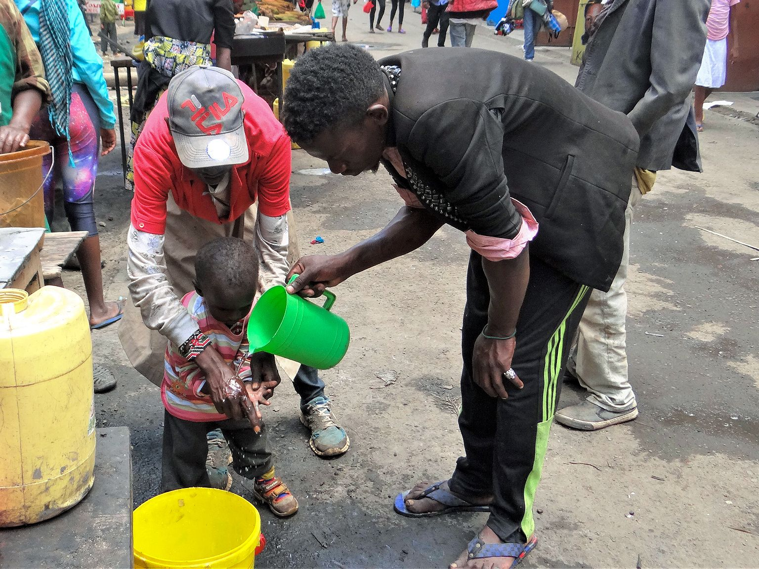 A photo of two men helping a small child wash his hands at a public station in the street