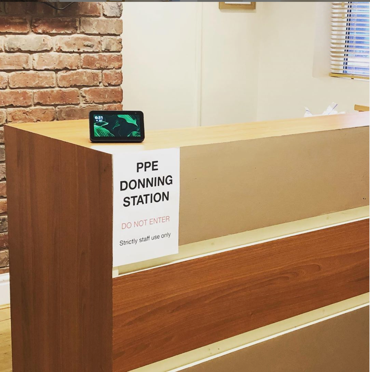 A photo of the PPE donning station at The Village Osteopaths, with a sign advising patients not to enter and a video device so Sean can carry out reception duties remotely