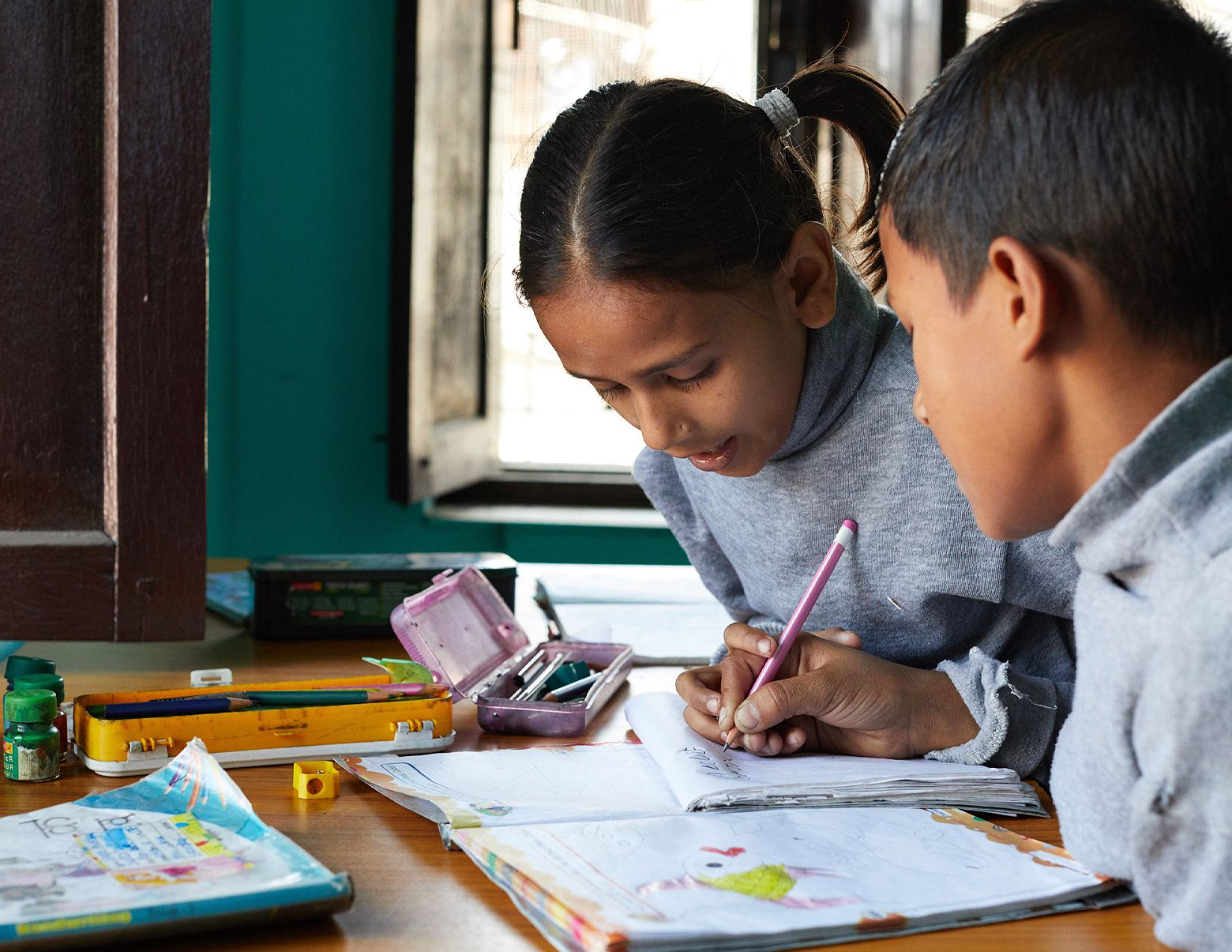 Two children at a Beyond the Orphanage home doing school work together.