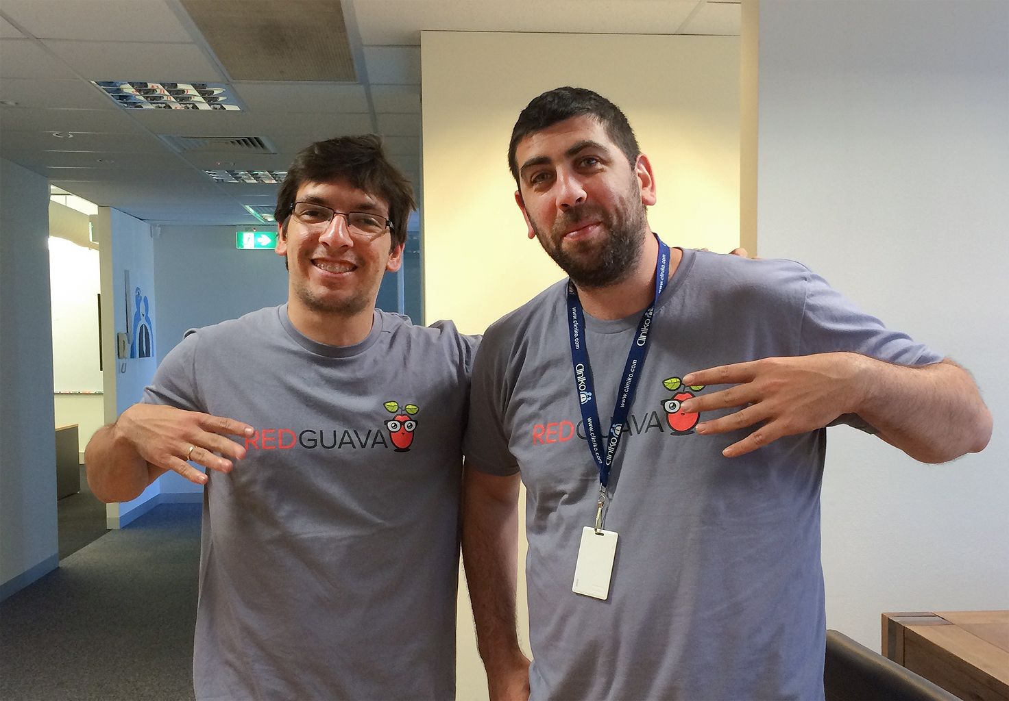 Two members of the Cliniko team wearing 'Red Guava' t-shirts in our first office in Melbourne.