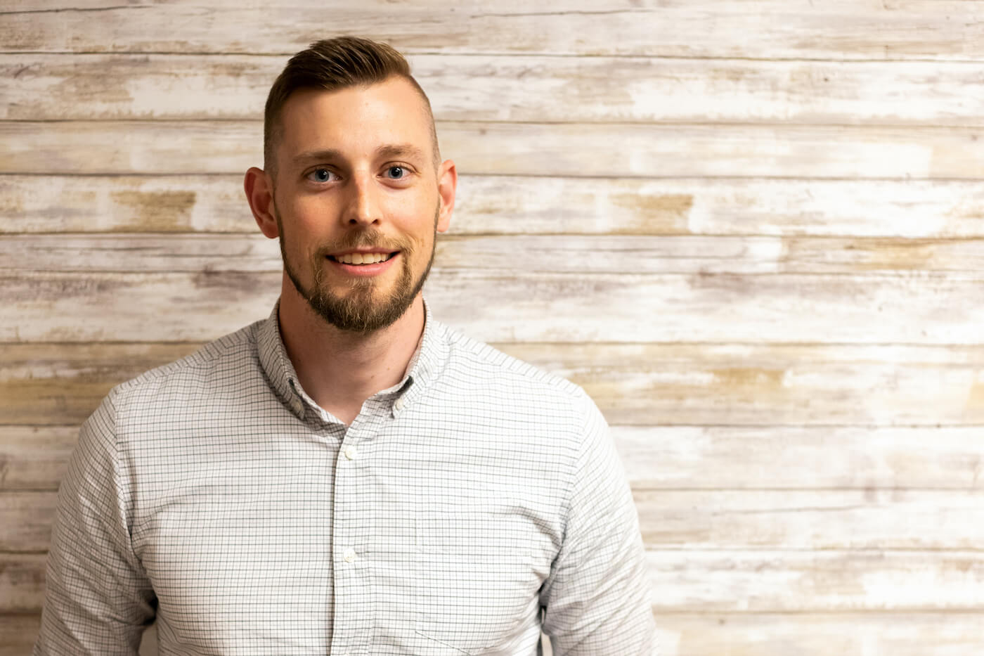 Dr Ben Tucker looking into the camera wearing a light-coloured plaid button-down shirt standing in front of a wall made of distressed wooden planks.