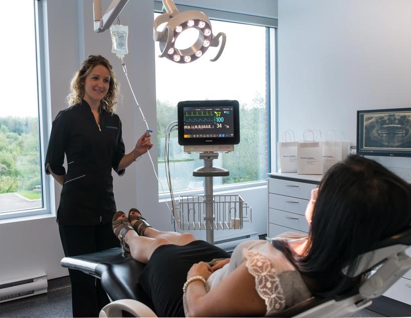 Photo montrant une infirmière avec une patiente qui est mise sous sédation à la clinique de Maxillo Québec.