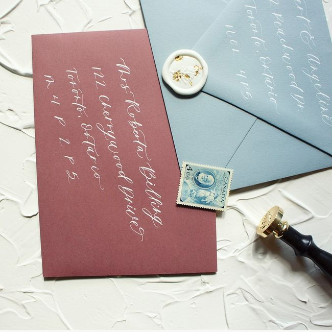 Dusty Blue Envelope and Rosebud Envelope, with white ink calligraphy, custom made wax seal with gold leaf accents and vintage postage stamps.