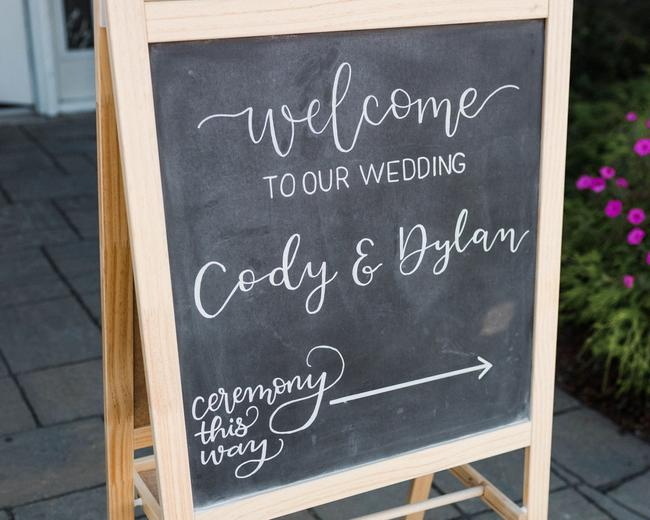 Large hand-lettered chalkboard easel wedding welcome sign, with the couple's names and wedding date written in calligraphy.