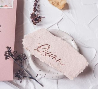 Personalized and hand painted place cards with orange watercolour paint.