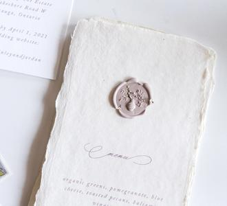 Handmade paper menus with dried floral wax seals
