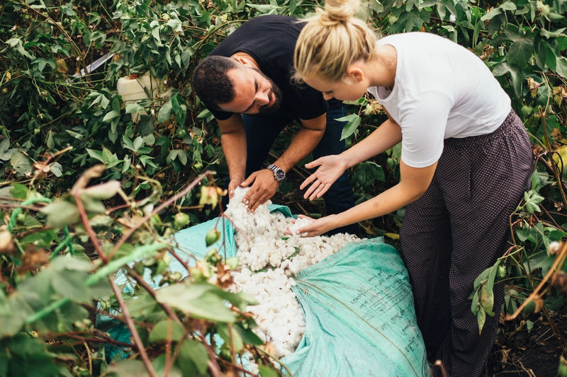 A photo of Rami Helali and Mackenzie Yeates inspecting a bail of Egyptian cotton at a Kotn farm.
