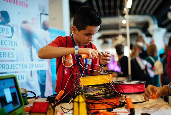 A boy holding some 3D printing plastic at a convention