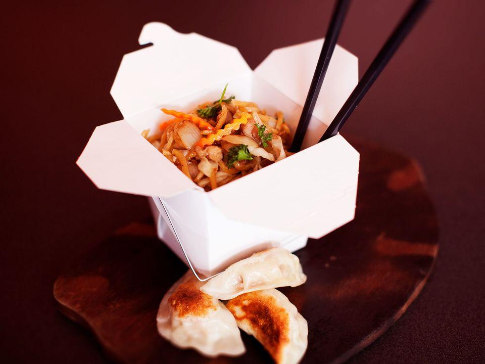 A takeaway box of Szechuan stir-fry and three dumplings.