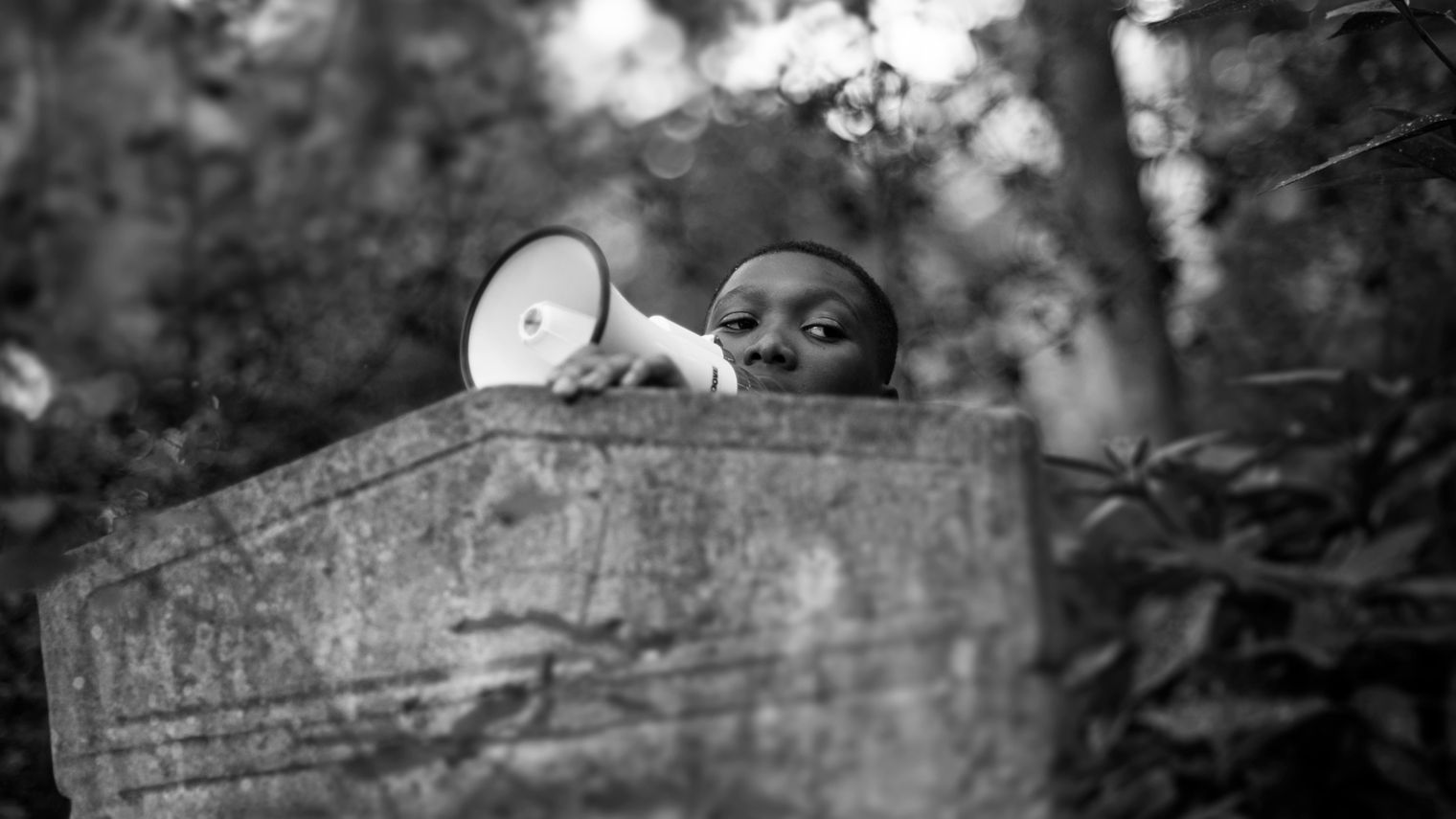 A teenager with a megaphone emerging from behind a gravestone.