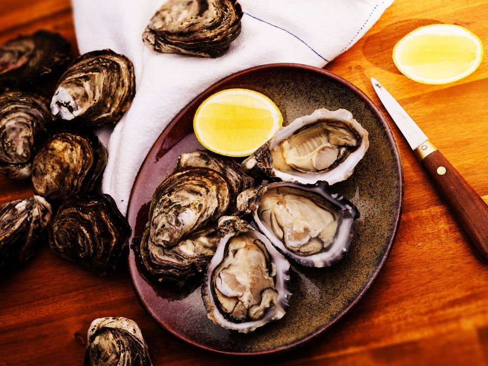 A plate of freshly-shucked oysters served with lemon.
