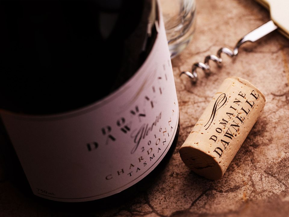A bottle of Domaine Dawnelle chardonnay, with the branded cork lying next to it.