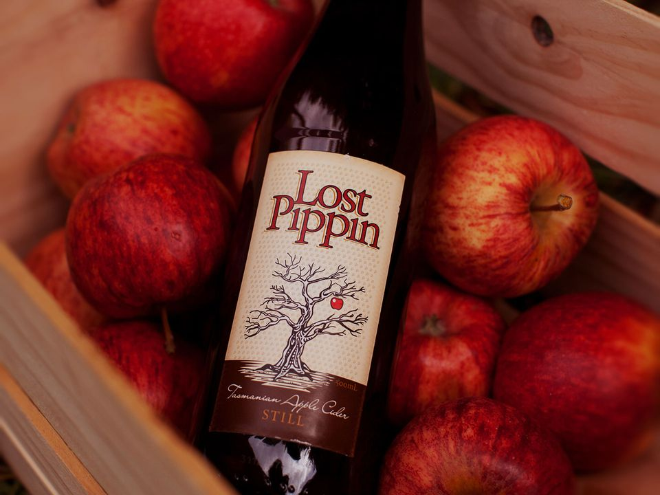 A bottle of Lost Pippin cider nestled in a crate of apples.