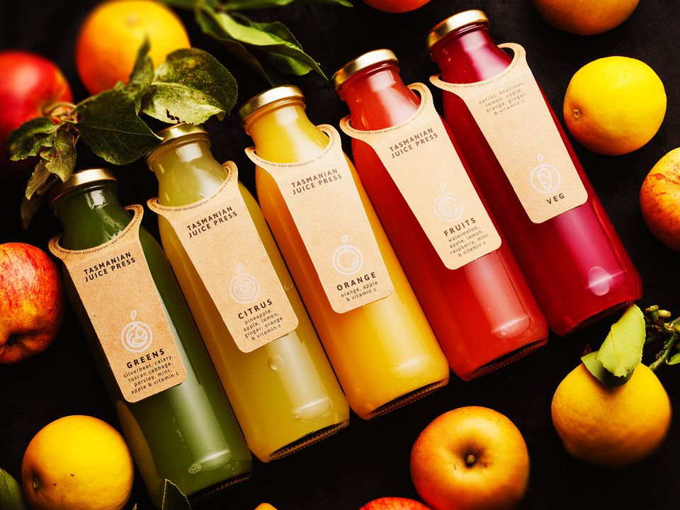 Five bottles of Tasmanian Juice Press juice, surrounded by fresh apples and lemons.