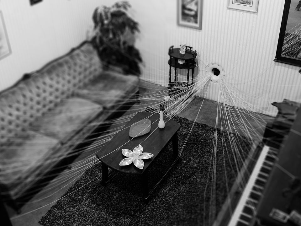 A living room whose contents are attached to a series of strings that exit through a hole in the wall.