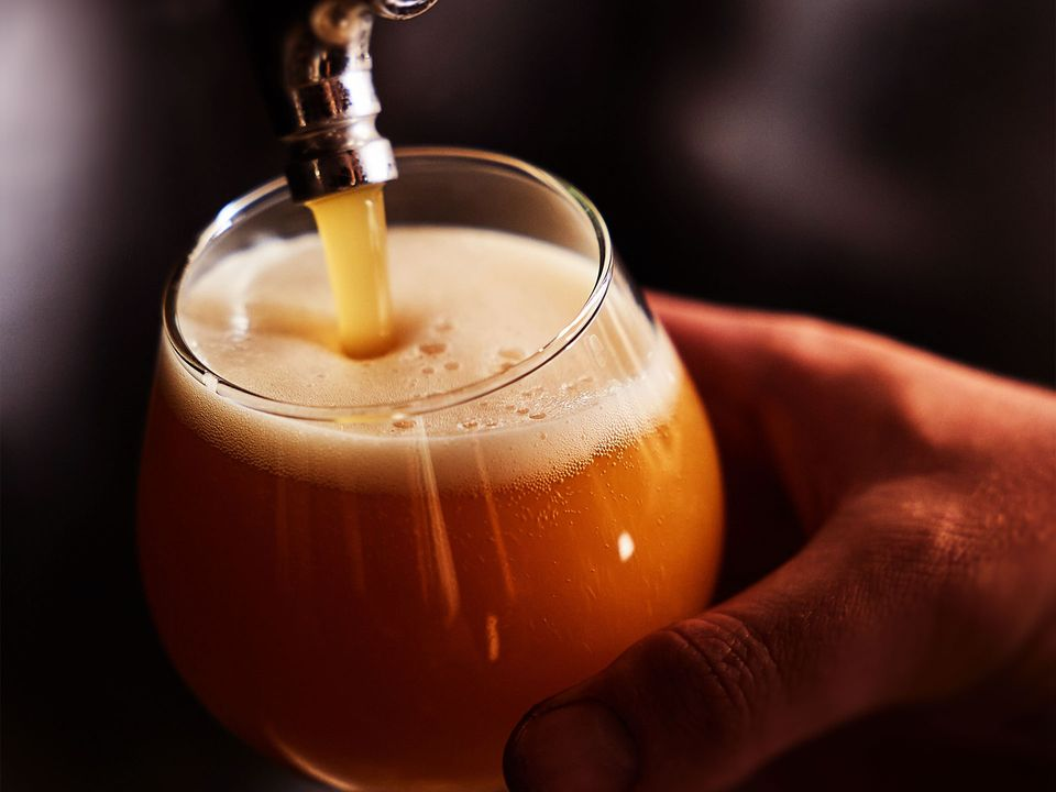 Craft beer being poured into a cold glass.