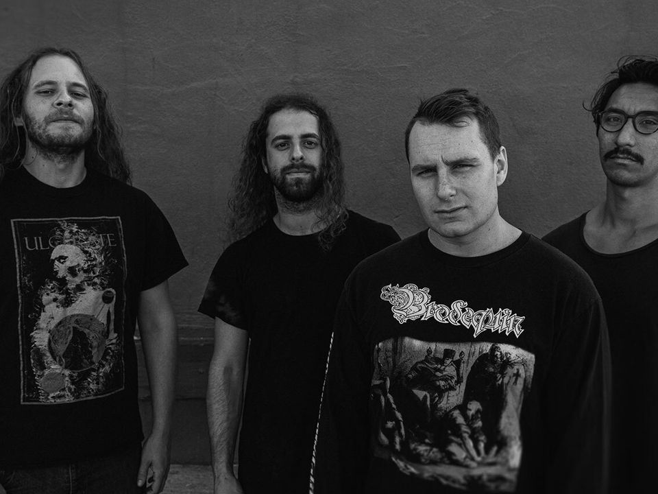 The four members of Disentomb standing against a wall.