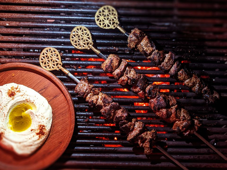 Three kebabs cooking on the grill, next to a side of hummus.