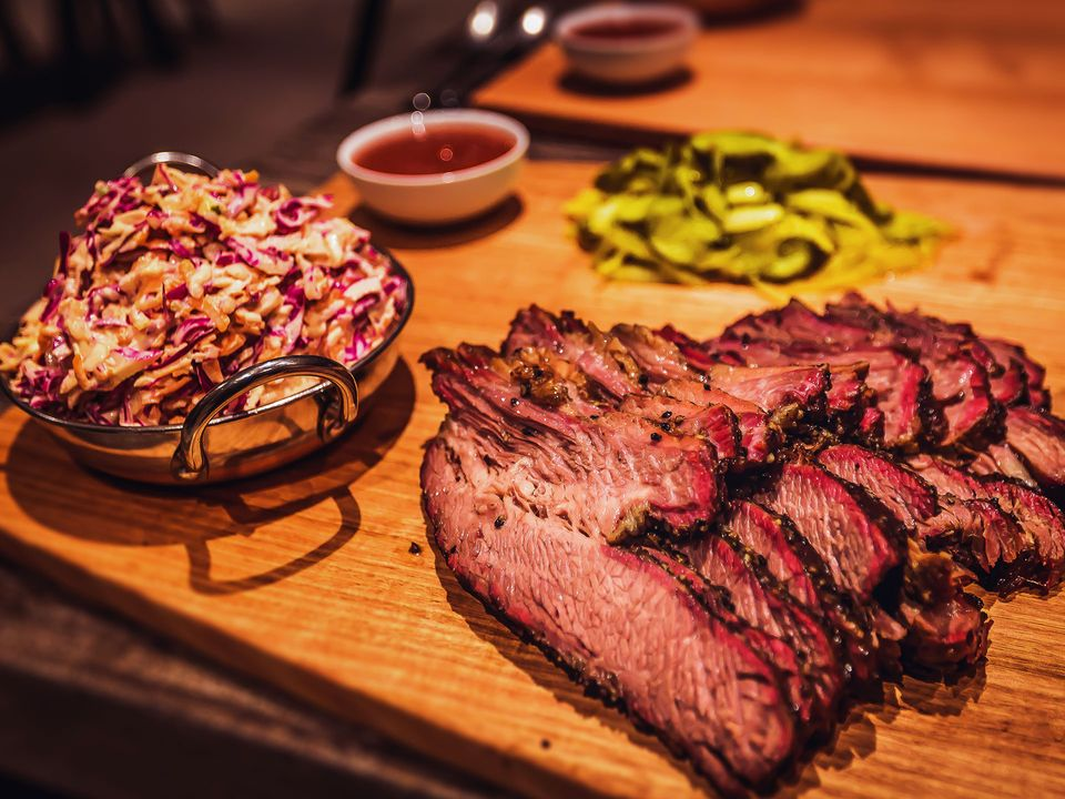 Slow, fire-cooked meats served with pickles and coleslaw.
