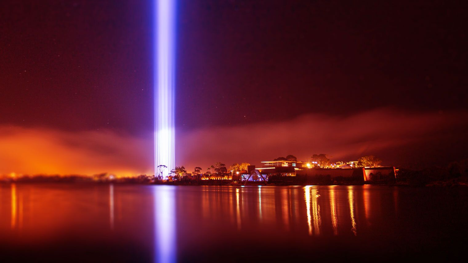 A great pillar of light reaching into the night sky, being reflected onto the Derwent River.