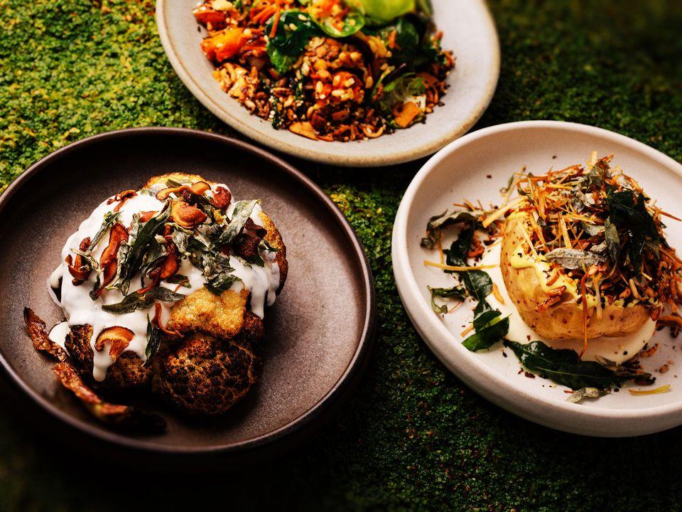 Three plates of roasted vegetarian food.