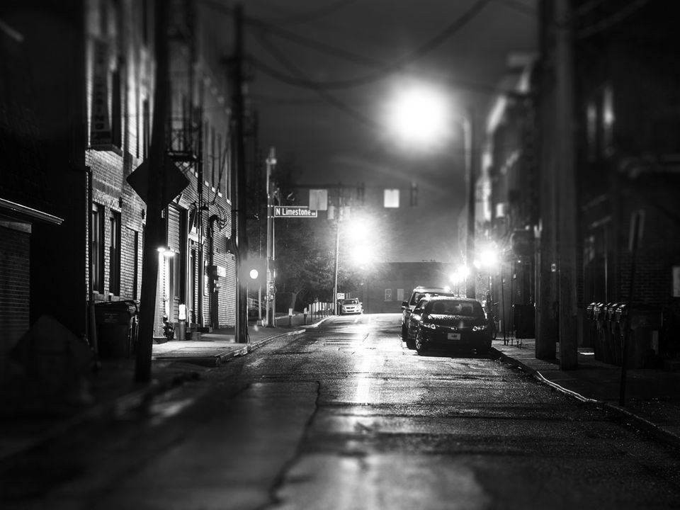 A suburban, nighttime vista: a dark stretch of road in town, lined by brick buildings and lit intermittently by street lamps, wet from the rain.