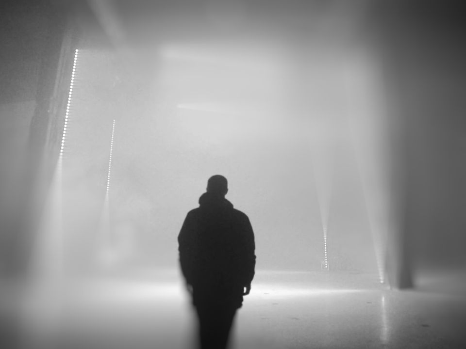 A man wearing a parka walks through a large, smoke-filled warehouse, lit intermittently by vertical rods of small, fluorescent globes.
