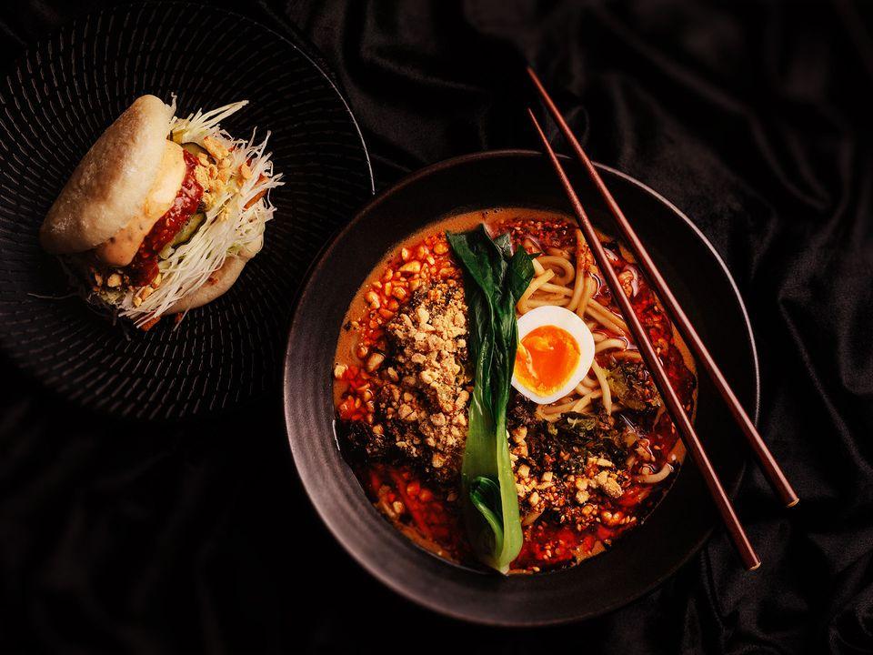 A bowl of sesame-chilli dan dan noodles topped with bok choi.