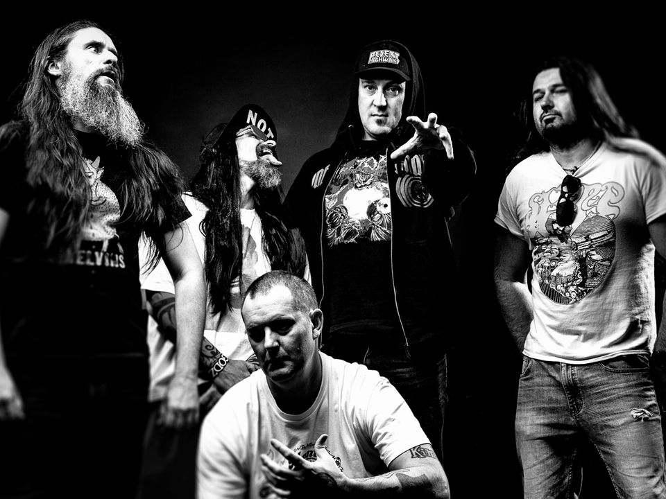 Five band members pose facing different directions in front of a black backdrop.