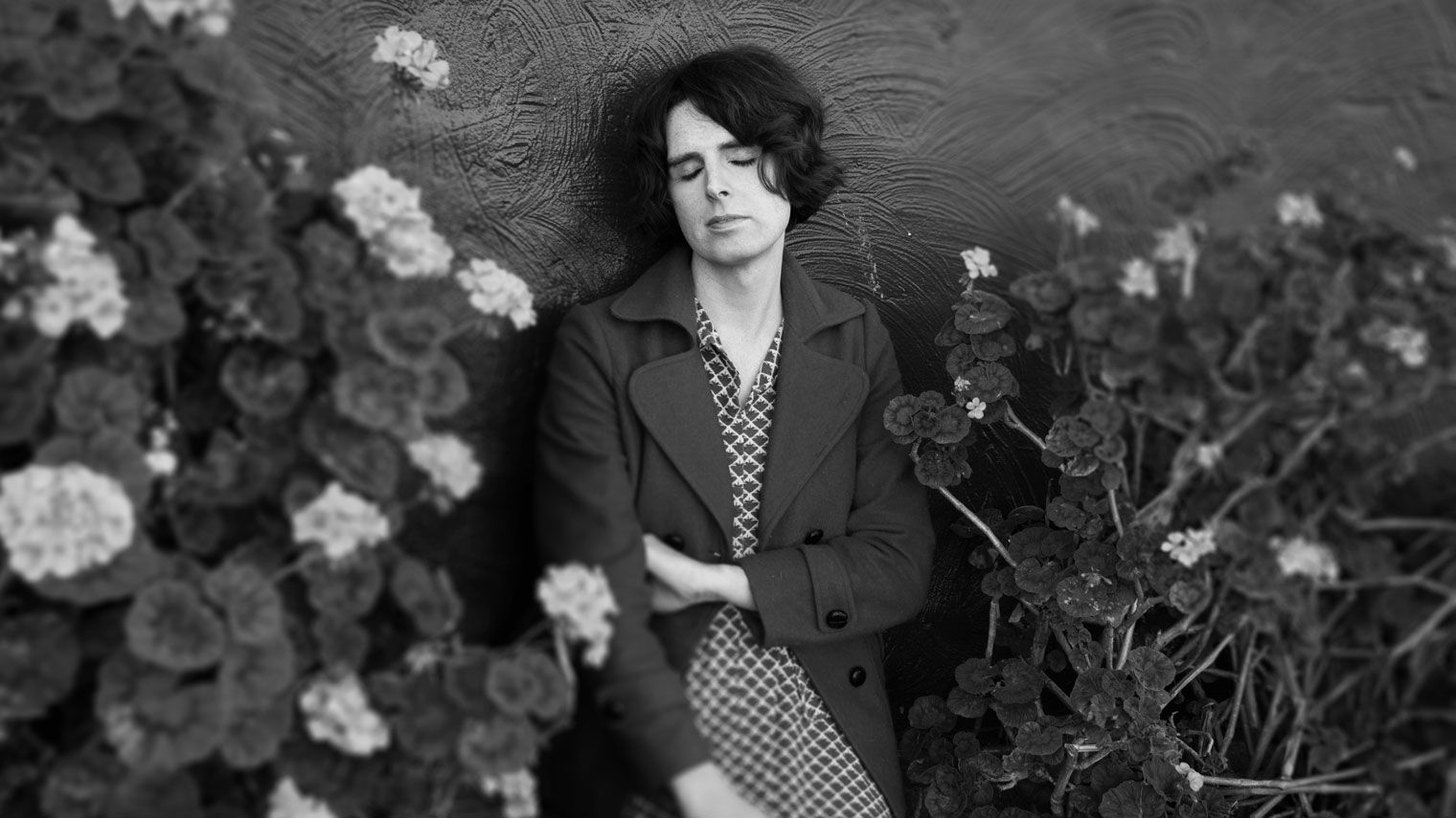 Chloe Alison Escott leans against a wall, eyes closed, surrounded by geranium bushes.