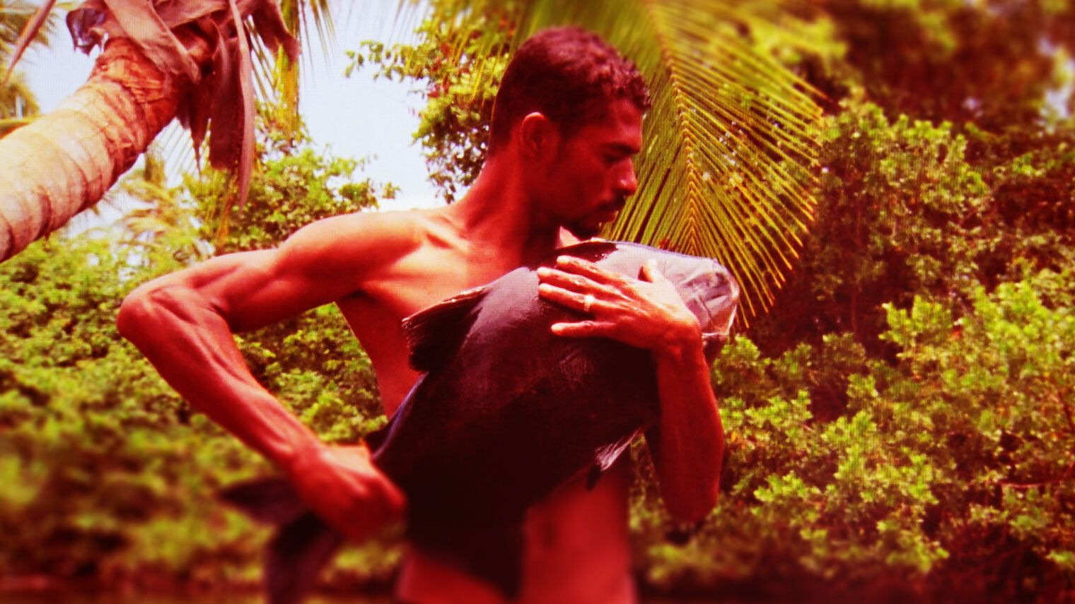 A river fisherman in remote Brazil cradles his dying catch in his arms.